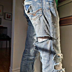 Pair of ripped, faded jeans pictured from the waist down, in a sunny living room