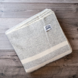 Folded wool blanket in light grey tweed with 2 white stripes