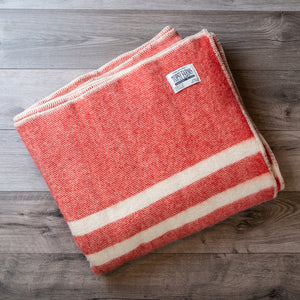 Folded wool blanket in red tweed with 2 white stripes