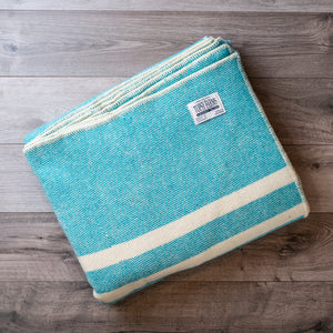 Folded wool blanket in turquoise tweed with 2 white stripes