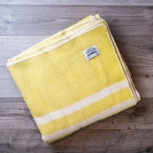 Folded wool blanket in yellow tweed with 2 white stripes