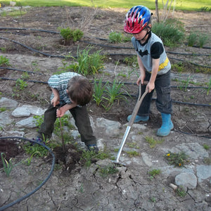 Two young boys wearing tee shirts, jeans, and rubber boots, digging in an unplanted garden