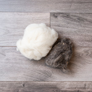 Two balls of unspun wool, one white and one dark grey, on a barnboard background