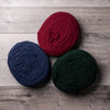 3 circular bundles of burgundy, navy, and dark green spun wool, on a barn board background