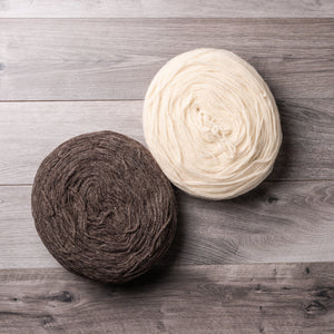 One white and one brown circular bundles of spun wool, on a barn board background