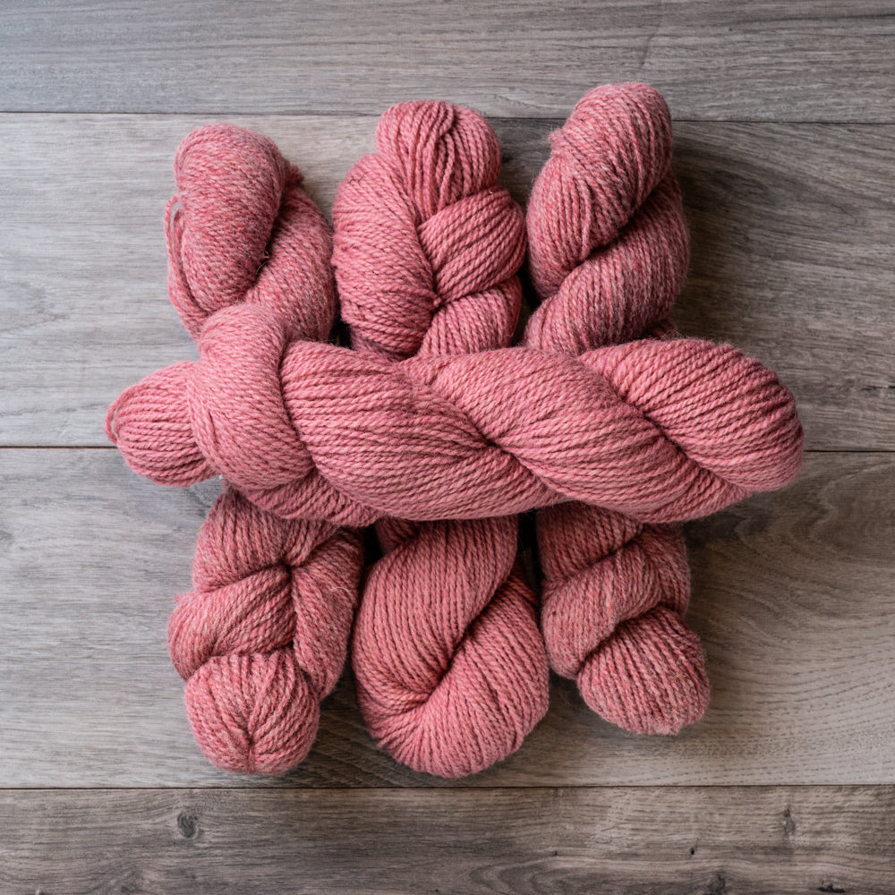 Skeins of dusty pink wool yarn on barnboard