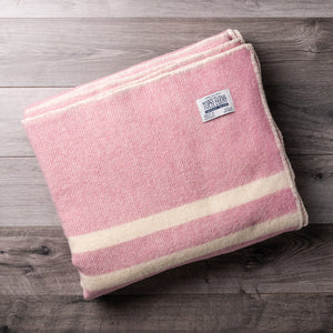 Dusty pink wool blanket with 2 white stripes and Topsy Farms tag in one corner, on a barn board background