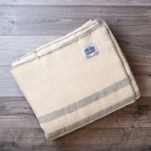 Light grey striped queen blanket made of natural wool.