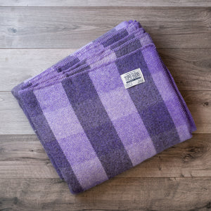 Folded wool blanket in a mauve and purple checkerboard pattern