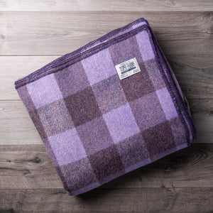 Mauve and mottled purple checkerboard wool blanket with Topsy Farms tag in one corner, on a barn board background