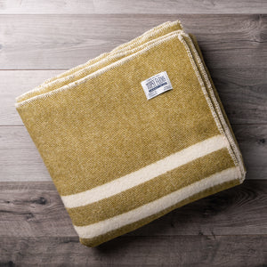 Olive green wool blanket with 2 white stripes and Topsy Farms tag in one corner, on a barn board background