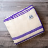 Folded wool blanked in natural white with 2 purple stripes