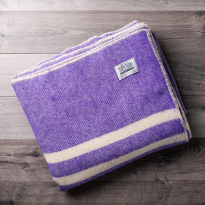 Rich purple tweed wool blanket with 2 white stripes and Topsy Farms tag in one corner, on a barn board background