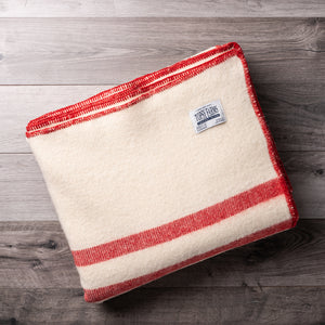 Creamy white wool blanket with 2 red stripes and Topsy Farms tag in one corner, on a barn board background