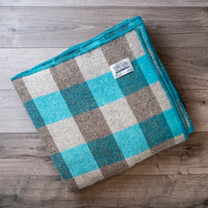 Folded wool blanket in a turquoise and light and dark grey checkerboard pattern