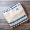 Natural white wool blanket with two royal blue stripes, and blue edging. Topsy Farms' label in one corner