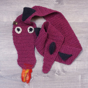Knitted burgundy dragon scarf, with black plates on the spine and fire coming out of its mouth. Made from Topsy Farms' wool