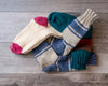 Knitted wool socks in a variety of colours, with stripes and contrasting heels and toes on barnboard backgroun