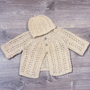 Hand knit natural white infant sweater and hat set, with 3 silver buttons in front.