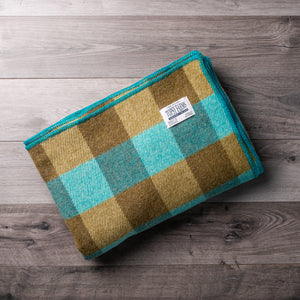 Turquoise and olive green wool blanket with Topsy Farms tag in one corner, on a barn board backgroun