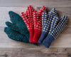 Green, red, and blue mittens with white accent Vs knitted throughout, on barnboard