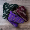 Dark green, purple, and burgundy knitted ankle-book style slippers with white accent Vs throughout, on barnboard