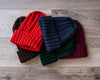 Red, navy blue, dark green, and burgundy knitted watch caps with brim folded up on barnboard