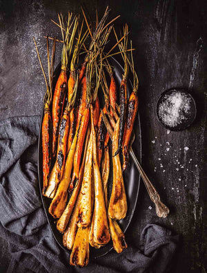 These maple glazed carrots with bourbon are made by roasting carrots and parsnips, if desired, and finishing them with a sweet and buttery bourbon, maple syrup, and apple cider vinegar glaze