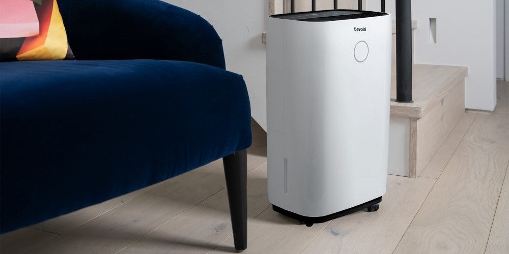 An image of a Devola Dehumidifier by a flight of stairs in a living room
