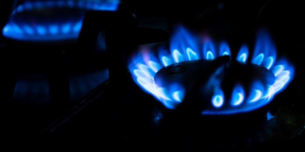 An image of an electric gas stove being switched on with a blue flame