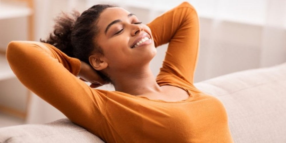 An image of a person relaxing and breathing in deeply at home