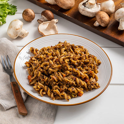 A bowl of ZENB Rotini Pasta mixed with mushrooms and ZENB Sweet Carrot and Tomato Marinara Pasta Sauce.