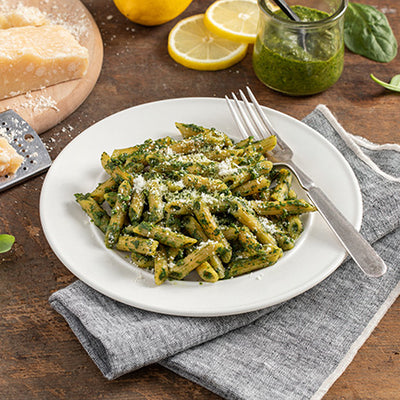 A bowl of ZENB Penne Pasta covered in Basil-Pesto sauce topped with Parmesan cheese.