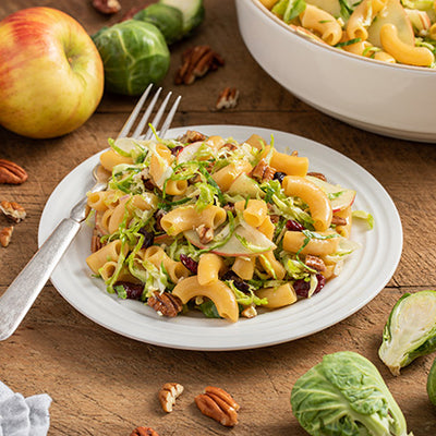 A plate of ZENB Elbow pasta with Brussel Sprouts, apples and cranberries topped with toasted pecans.