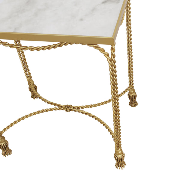 A combination of twisted metal rope and small metal tassels make up a unique accent table topped with a natural marble