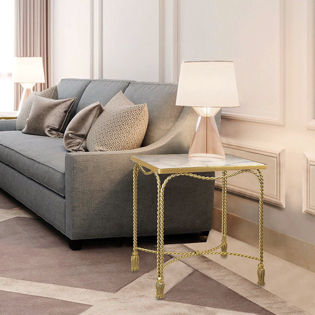 A unique golden accent table inspired by twisted rope stands by the end of a blue couch
