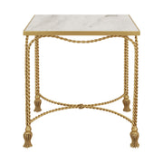 Wavy golden metal ropes and golden tassel feet make up the base of a luxury end table topped with a rectangular piece of natural marble