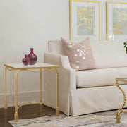 Twisted metal rope-themed side table in golden color and marble top stands at the end of a pink sofa
