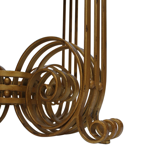 A detailed shot of a luxury table showing several layers of wrought iron scrolls in an antique gold finish