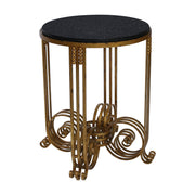 An accent table inspired by the 'Art Deco' movement which has an antique gold base and a black granite top