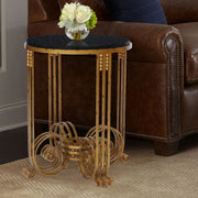 An Art Deco styled end table made of wrought iron and topped with a round black granite stands by a leather couch