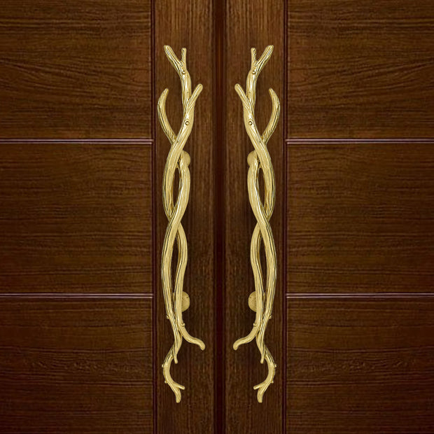 A pair of golden accent pull handles inspired by twisted branches mounted on a closed wooden door