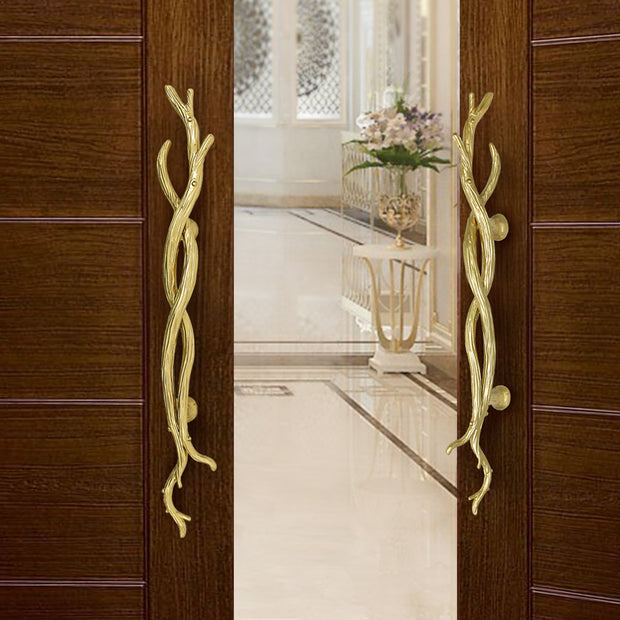 A pair of golden accent pull handles inspired by twisted branches mounted on an opened wooden door
