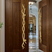 A pair of golden decorative pull handles inspired by twisted branches mounted on an opened wooden door
