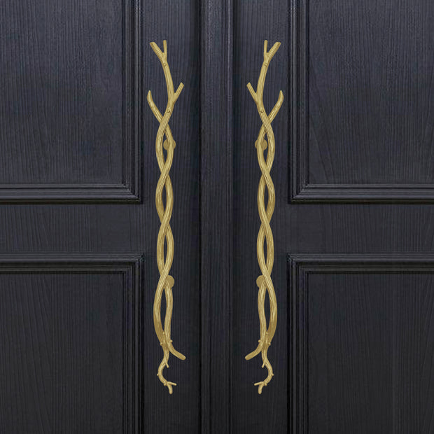 A pair of decorative golden pull handles inspired by twisted branches mounted on a closed wooden door