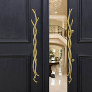 A pair of accent golden pull handles inspired by twisted branches mounted on an open wooden door