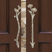 A pair of antique white decorative accent pull handles inspired by flowers mounted on an opened wooden door