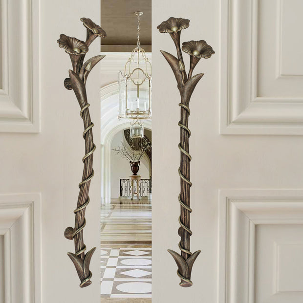 A pair of dark bronze accent pull handles inspired by flowers mounted on an opened wooden door