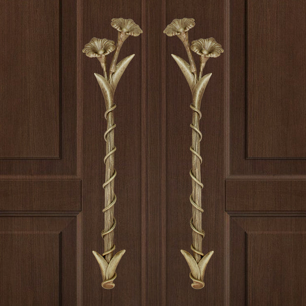 A pair of light bronze decorative accent pull handles inspired by flowers mounted on a closed wooden door