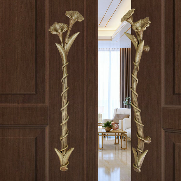 A pair of light bronze accent pull handles inspired by flowers mounted on an opened wooden door